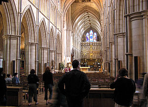 This longshot of the interior of Southwark Cathedral shows both the nave, with crisply detailed pointed arches, and the older structure beyond. A number of visitors are silhouetted against the pale stone.