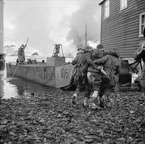 A black and white photograph of a wounded soldier being helped to a landing craft by two other soldiers