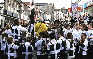 A street lined with shops is filled with hundreds of people. In the foreground are children wearing black vests each one defaced with a large white cross. The children surround a fiddler. In the background are spectators.
