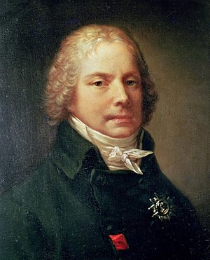 Portrait of a man, showing his head and shoulders. He is wearing a black jacket with a high-necked collar and a white shirt tied in a bow. His head is adorned by a curly blonde wig.