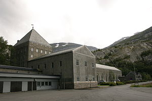 Large dark building with snow-capped mountains at the rear
