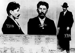 Set of three photographs and a filled form, all profiling a man with a thick mustache and dark hair, dressed in a hat, black overcoat, white shirt, black pants and black shoes.