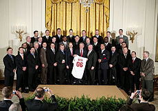 "Three rows of men in various dark-colored suits; in the center, a gray-haired smiling man holds a white baseball jersey that reads ""Bush"" on the back in small red print with ""06"" in larger red print below it."