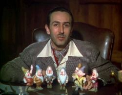 A color photograph of Walt Disney sitting behind a desk. Seven figurines are standing before him.