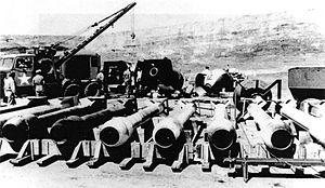 Long, tube-like casings. In the background are several ovoid casings and a tow truck.