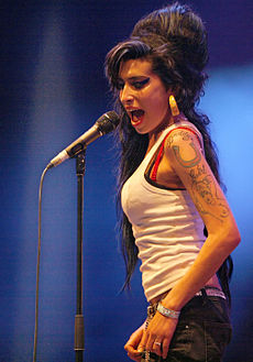 Amy Winehouse performing on 29 June 2007 at the Eurockéennes music festival in eastern France. Winehouse is looking into the crowd while singing sidelong into a handheld microphone. Her black hair is combed back in a relaxed style. Her tattooed shoulder is bare and she is wearing large, chunky earrings.