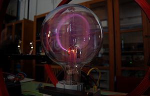 A round glass vacuum tube with a glowing circular beam inside