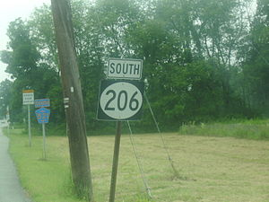 A roadside shield in the foreground reading south Route 206 with a shield for south Sussex County 521 in the distance