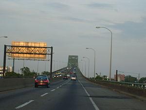A four lane freeway ascending onto a continupus arch bridge