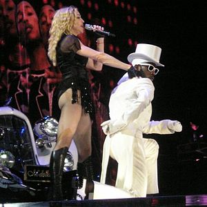 A faraway image of a female blond woman on stage in front of a white Speedster. The woman is wearing a white hat, black top and dancing. Two huge backdrops display two African American males in front of blinking lights. The one in the top backdrop looks towards the camera and smiles and the one in the bottom backdrop is looking down while wearing a white-rimmed sunglass.