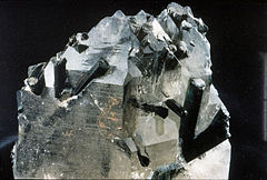 Dark bluish and green or black, rod-like tourmaline crystals emerging from clear quartz holding matrix.