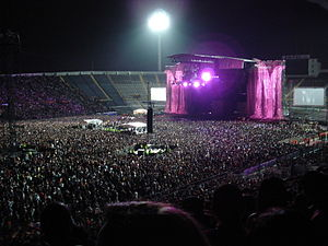 A stadium filled with spectators on the podiums and on the ground. In the middle is a stage with two giant pink 'M' symbols flanking it. A large flood light is visible behind it.