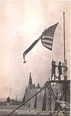 photograph of a walled fort with three Marines raising an American flag over it