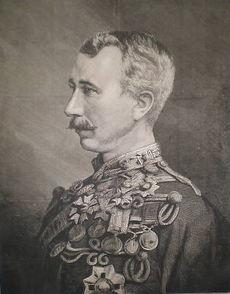 A moustachioed man with closely cropped hair and a chest covered in military medals