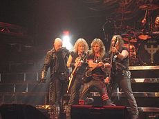 Four men standing next to one another on a stage, three of which are holding guitars. All four men are wearing black clothing, and some of the articles of clothing are studded.
