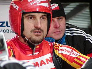 A man with a goatee wears a red-white-and-yellow tight jumpsuit, with a red-and-white vest over it, and a red helmet with a raised full-faced visor. He shows a concentrated look. Partially hidden behind him is another man, wearing a black tracksuit jacket and winter cap.