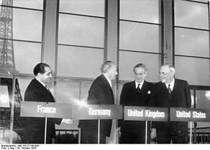 Four men stand behind podiums with their country names of France, Germany, United Kingdom and United States, in front of a backdrop of the Eiffle Tower.