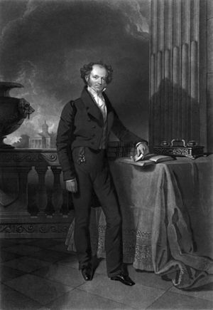 Engraved full-length portrait of a balding man standing next to a table with his left arm resting on a book and in the background a stone balustrade beyond which are trees and a building with columned portico