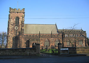A stone Gothic church with battlemented parapets and tower
