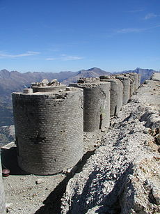 A row of round brick turrets can be seen in the foreground. A mountain range occupies the background.