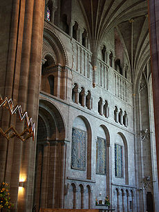 A transept interior with a wall panelled with shallow Norman arches and open galleries.