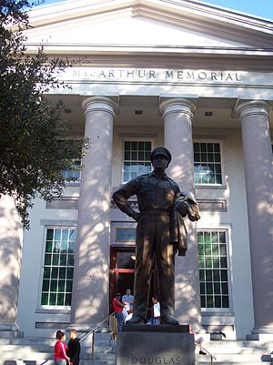 "A large bronze statue of MacArthur stands on a pedestal before a large white building with columns. An inscription on the building reads: ""Douglas MacArthur Memorial""."