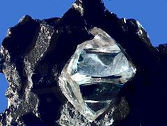 A clear octahedral stone protrudes from a black rock.