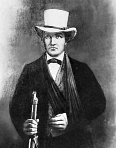 A man in a dark suit with a white hat. His left arm seems to be in a sling. In his right hand he grasps the barrel of a rifle.