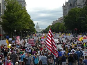 photograph of thousands of people some holding American flags