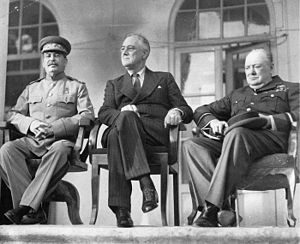 Three men, Stalin, Roosevelt and Churchill, sitting together elbow to elbow