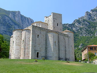 A small church sits on a steep rise, surrounded by craggy mountains. It is basically square with three bulging projections and a castle-like tower.