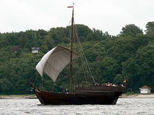 A photograph of a small wooden ship with white sail traversing an estuary; behind the ship is a wooded shoreline.