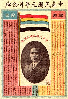 A calendar with a picture of a Chinese man in the centre. On top of it stands a flag with five horizontal stripes (red, yellow, blue, white, and black).