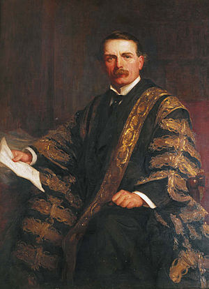 A man in his late 40s, with brown hair and moustache, wearing a black suit, white wing-collared shirt and black tie, together with a black gown repeatedly patterned in gold brocade; he sits in a chair, holding a piece of paper in his right hand