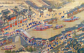 A painting in which a yellowish river flows diagonally from the bottom left to the top right, with one road on each side. On the side of both roads are gray-roofed houses. Those on the other side of the river have counters that open directly on the river. There are dozens of people dressed mostly in blue on both roads and crossing a bridge in the foreground. Several barges with canopies are on the water.