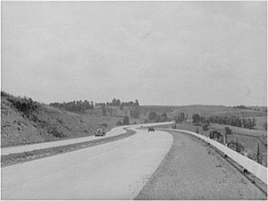 Black-and-white photo of four-lane highway, with one car in each direction