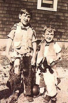 A black and white photograph of two young children aged approximately six and three dressed as cowboys
