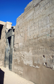 Ground-level outside view of stone walls with raised-relief carvings of human figures and hieroglyphic writing; a doorway is positioned at the center; the top left portion shows a blue sky without clouds.
