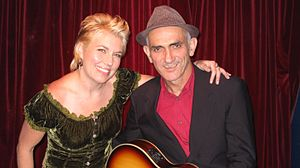 Upper body shot of a woman with Kelly. Both are smiling; she has her left arm across his back to his left shoulder. Kelly is wearing a hat, black jacket, and red shirt and is cradling a guitar (mostly out of view).