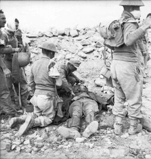 A German doctor and a British soldier kneel over a wounded German soldier who is laying on the ground. Three soldiers, one of whom appears to be wounded, stand to the left while two more soldiers stand to the right.