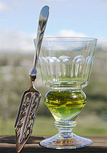 A reservoir glass filled with a naturally colored verte absinthe next to an absinthe spoon