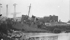 ship at 45 degree angle showing damage caused by German gunfire and impact with the dock