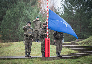 Three soldiers in camouflage stand in salute while a forth raises a blue and white flag on a red and white stripped flagpole.