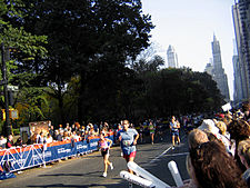 Three runners in a race down a street where onlookers are cheering behind barriers.