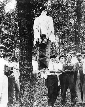 Leo Frank's corpse hanging from a tree after the lynching. His hands and feet bound. A crowd of spectators surrounds the tree.