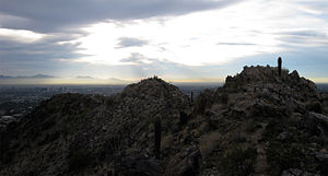 a view of the craggy tops of two small mountain peaks in the Phoenix Mountain preserve, with the city of Phoenix in the background.