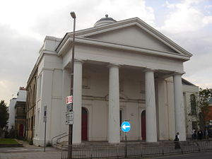 A Classical style, stuccoed building whose façade is dominated by four tapering columns supporting a pediment. The side wall is yellow brick. Partly hidden behind the columns are two red round-headed doors. Above the pediment is a partly hidden cupola. A modern extension is partly visible to the right.