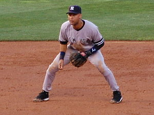 "Baseball player in an athletic stance. He is wearing a blue baseball cap, and a grey jersey with the words ""New York"" inscribed."