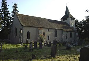 Photograph of a church with roughcast walls and square belltower. A number of gravestones are visible in the foreground