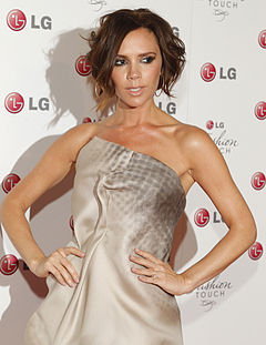 Victoria Beckham posing on a red carpet at an event, wearing a creme colour dress and neutral colour makeup.